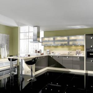 Meble kuchenne z programu IM 2800. Szare fronty wykończone są lakierem w wysokim połysku. W duecie z magnolią, również w wysokim połysku, stworzył niezwykle zgrany duet, który pięknie prezentuje się na tle zielonej ściany. Wycena indywidualna, Impuls.