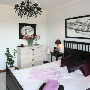 Podłoga w sypialni wykonana z dębu rustykalnego bejcowanego na biało świetnie współgra z jasnymi ścianami i mocnymi akcentami w postaci wyposażenia. Fot. Bartosz Jarosz.