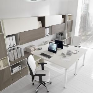 Jasne biuro ożywiają fronty regału w kolorze ciemnego drewna. Fot. Giessagi.