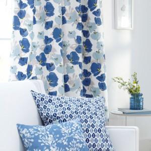 Niebieskie kwiaty na zasłonach korespondują z dekoracyjnymi poduchami. Fot. Romo.