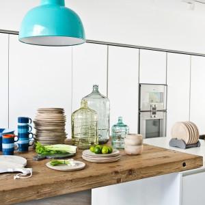 Blat roboczy będący przedłużeniem wyspy oświetla ozdobna lampa w turkusowym kolorze. To świetne rozwiązanie w kuchni otwartej na salonu. Fot. HK Living.