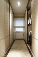 """Po obu stronach długiej garderoby wbudowano wielkie szafy o rozsuwanych drzwiach. Ich fronty zostały w pomysłowy sposób pokryte tkaniną – jasnym płótnem z charakterystycznym """"ślimakowym"""" deseniem, nadającym wnętrzu nieco romantyczny charakter.Fot. Bartosz Jarosz."""