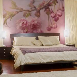 Fototapeta przedstawiająca gałązkę z kwiatowymi pąkami w powiększeniu poprzez umieszczenie tylko za łóżkiem wyznacza strefę spania w sypialni. Fot.Big Trix.