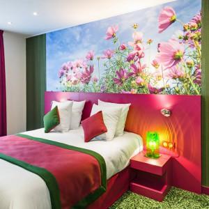 Kolorowe kwiaty na tle błękitnego nieba w połączeniu z różowymi meblami oraz kolorowymi tkaninami tworzą energetyczną kompozycję.Fot. Le jardin de Montmarte Hotel.