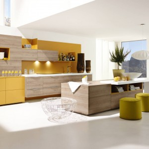 Meble kuchenne z kolekcji Alnoplan. Kolor żółty ładnie koresponduje z frontami wykończonymi drewnopodobnym dekorem o fakturze buku. Wyspa stanowi element oddzielający kuchnię od części wypoczynkowej. Wycena indywidualna, Alno.