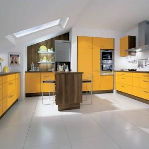 Funkcjonalne meble kuchenne z programu IP 1200. Fronty w słonecznym, żółtym kolorze tworzą zgrany duet z elementem wykończonymi drewnopodobnym dekorem. Wycena indywidualna, Impuls.