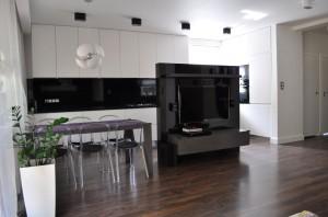 Kuchnia połączona z salonem dzięki konsekwentnemu zastosowaniu barw stanowi z nim jedną całość dzięki czemu dwie strefy przenikają się wzajemnie.