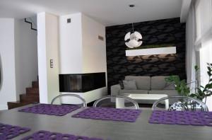 Strefa salonu posiada minimalną ilość mebli, gdyż rolę miejsca do składowania przedmiotów w całości przejęła ogromna i ergonomicznie zaprojektowana kuchnia.