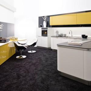 Meble kuchenne z kolekcji Nova Lack. Fronty w ładnym, energicznym, żółtym kolorze wykończone są lakierem w wysokim połysku, który tworzy niezwykle ciekawy kontrast z duetem bieli i czerni, również w połysku. Wycena indywidualna, Nolte Küchen.
