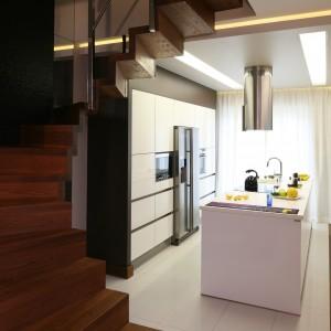 Centralnym punktem kuchni jest duża wyspa. Umieszczone są w niej liczne szafki, szuflady, zmywarka, zlewozmywak oraz płyta indukcyjna. Projekt: Chantal Springer. Fot. Bartosz Jarosz.
