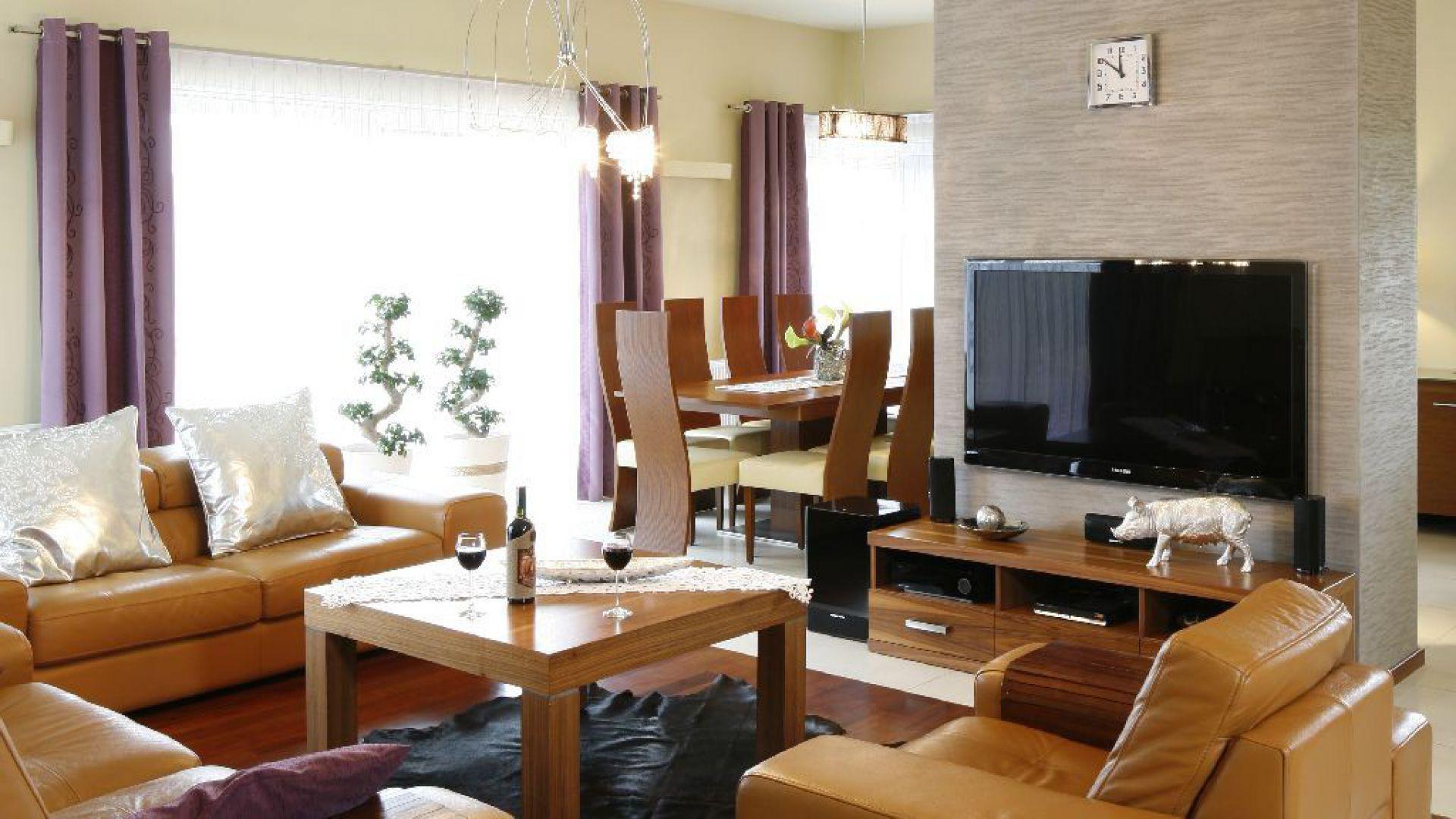 Pomysł do dużego pokoju: dwie sofy i fotel ustawione wokół stolika kawowego niedaleko kominka. Proj. wnętrz arch. Piotr Stanisz. Fot. Bartosz Jarosz.