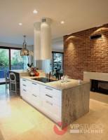 Kuchnia klasyczna z nowoczesnymi dodatkami.  Jasna kolorystyka w połączeniu ze ścianą z cegły tworzą wrażenie przytulności i ciepła.