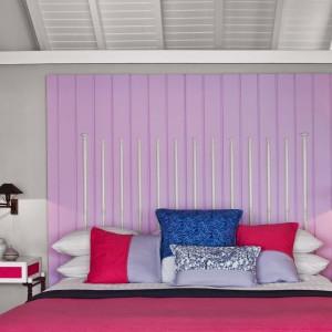 Ściana wpadająca w pastelowy fiolet w połączeniu z różowymi tkaninami tworzy spójną kompozycję. Fot.Luis Pons Design Lab.
