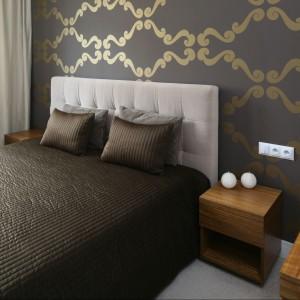 Prosty, pikowany zagłówek z jasną tapicerką kontrastuje z ciemną tapetą ze złotym ornamentem. Proj.Małgorzata Galewska. Fot.Bartosz Jarosz.