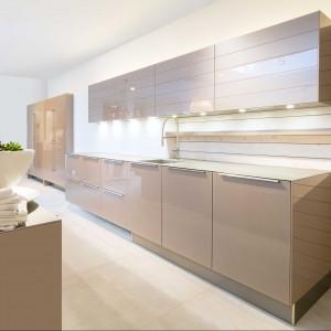 Kolejna propozycja to kuchnia w kolorze złotego brązu. Model AV5090 z frontami ze szkła w kolorze Goldbronze metallic z blatami roboczymi ze spieków kwarcowych o grubości zaledwie 7 mm. Tak mała  grubość blatu nadaje kuchni lekkości, a jednocześnie ten materiał jest całkowicie odporny na zarysowania i zapewnia doskonałe warunki do pracy w kuchni. Sprzęt AGD jest  zabudowany i niewidoczny - schowany w wysokich szafach za przesuwanymi drzwiami. Nad płyta indukcyjna umieszczony jest szklany okap w formie wiszącej nad blatem lampy. Fot. Lome Meble.