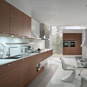 Kuchnia z frontami z naturalnego forniru z drewna orzechowego. Model AV5080 Nussbaum-fineline w połączeniu z białymi blatami w kolorze Bianco Zeus to bardzo klasyczne i eleganckie  zestawienie. Całość dopełnia szkło między blatem a szafkami górnymi w kolorze Brilantweis z listwą aluminiową na akcesoria kuchenne. Dolne szafki szufladowe podniesione wysoko nad podłogą optycznie dodają lekkości całemu pomieszczeniu. Szklany stół i designerskie krzesła nadają ostatni szlif i doskonale się komponują z zabudową kuchenną. Fot. Lome Meble.