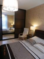 Beżowa sypialnia z dekoracyjnymi motywami.