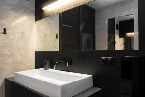Łazienka ukazuje zróżnicowane faktury ścian i podłogi. Stiuk w połączeniu z unikatowymi, czarnymi płytkami doskonale ze sobą współgrają.