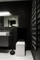 W niewielkiej łazience zastosowano rozwiązania optycznie zwiększające przestrzeń. Duże lustra i przeszklenie pod prysznicem dają uczucie przestrzeni.