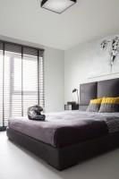 Sypialnia z wygodnym, tapicerowanym łóżkiem, nad którym zawisła kontrowersyjna grafika Banksy'ego jest przytulna mimo surowego charakteru.ygodnym, tapicerowanym łóżkiem, nad którym zawisła kontrowersyjna grafika Banksy'ego jest przytulna mimo surowego charakteru.