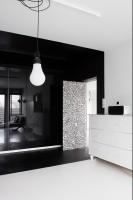 Ściany i sufit pomalowane są matowymi farbami ceramicznymi, a szafy z frontami o wysokim połysku działają jak lustro i optycznie powiększają to stosunkowo niewielkie wnętrze. Za licowanymi drzwiami kryje się przejście do pracowni właścicielki.