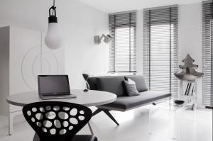 Strefa biała, dzienna służy również do pracy. Wygodny, okrągły stół pozwala na przemieszczanie się z komputerem w poszukiwaniu inspiracji. Lampka Trash Me od AndTradition została w niestandardowy sposób powieszona na ścianie, dając wieczorem przyjemne, nastrojowe światło.