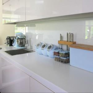 Blat roboczy w kuchni wykonano z Corianu®, wpuszczono pod niego płytę gazową Viking Professional. Z oferty tej samej marki pochodzi metaliczny okap i reszta AGD. Fot. Bartosz Jarosz.