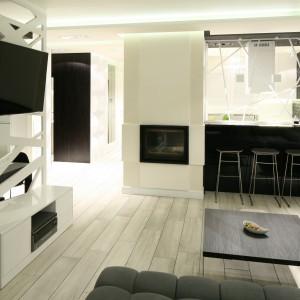 Białe fronty szafek wykonane z lśniącego akrylu kontrastują z ceglaną ścianą pomalowaną czarną farbą. Na czarno wykończono także wysoki barek widoczny od strony salonu. Projekt: Dominik Respondek. Fot. Bartosz Jarosz.