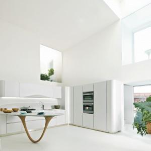 Kuchnia z kolekcji Ola20 o ładnych, opływowych kształtach. Białe fronty wykończone lakierem w połysku tworzą haromijną całość z kamiennym blatem, również w kolorze białym. Wycena indywidualna, Snaidero.