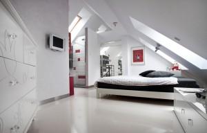 Poddasze jest jedną dużą, otwartą przestrzenią. Pomiędzy sypialnią, a łazienką nie ma drzwi, a okna dachowe oświetlają wnętrze przyjemnym światłem dziennym.