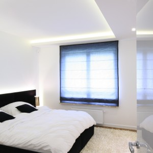 Białe ściany i podłoga tworzą tło czarnego, tapicerowanego łóżka i okiennej dekoracji. Proj. Agnieszka Hajdas - Obajtek. Fot.Bartosz Jarosz.