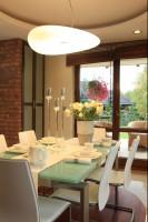 Szklany stół kontrastuje z ciemną zabudową kuchenną oraz ceglanymi ścianami. Fot. Green Canoe.