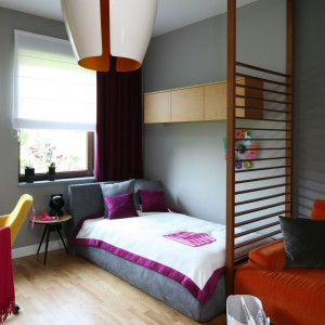 Szare łóżko ożywia fiolet poduszek i lamówek narzuty. Fot. Bartosz Jarosz.