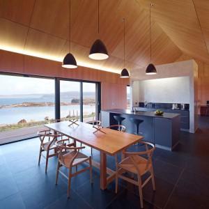 W tym drewnianym domu z pięknym widokiem za oknem, który znajduje się w Szkocji, kuchnia jest nie tylko nowoczesna, ale wręcz minimalistyczna. Jej prosta aranżacja pasuje jednak do stylistyki całego domu. Projekt: Dualchas Architects. Fot. Dualchas Architects.