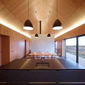 Widok z kuchnia na jadalnię. Stół i krzesła są wprawdzie drewniane, ale całość wciąż pozostała w minimalistycznej oprawie. Projekt: Dualchas Architects. Fot. Dualchas Architects.