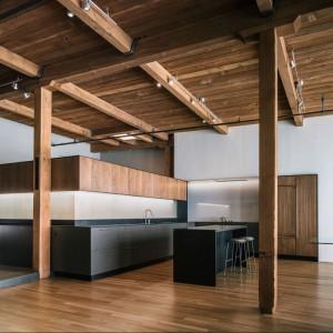 Szarą, minimalistyczną kuchnię pięknie ocieplają drewniane elementy. Kolor biały dodatkowo dodaje jej lekkości i optycznie powiększa otwartą przestrzeń. Całość tworzy ładną aranżację i na pewno spodoba się miłośnikom nowoczesnego stylu. Projekt: Line Office. Fot. Line Office.