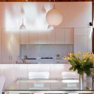 Biała zabudowa kuchenna nadaje przestrzeni lekki, stylowy klimat. Projekt: Searns Studio. Fot. Searns Studio.