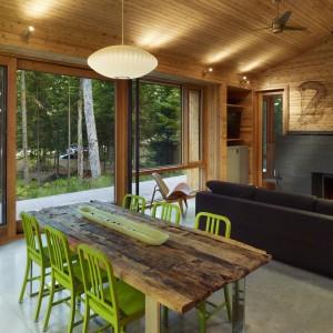 Do drewnianego, prostego stołu dodano lekkie krzesła w kolorze zielony, które ożywiają spokojną przestrzeń. Projekt: Sperkul. Fot. Sperkul.