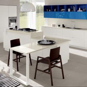 Meble kuchenne z kolekcji Mood o prostej formie. Białe, matowe fronty pięknie łączą się z niebieskimi w połysku. Centralnym punktem kuchni jest funkcjonalna wyspa, która połączona została ze stołem. Wycena indywidualna, Scavolini.