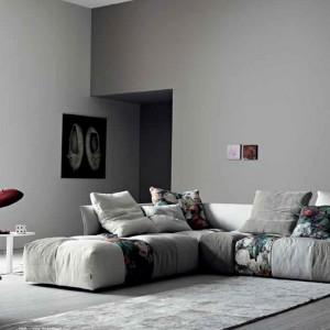 Bordowa lampka oraz kwieciste detale na sofie ożywiają szare pomieszczenie. Fot. Saba.