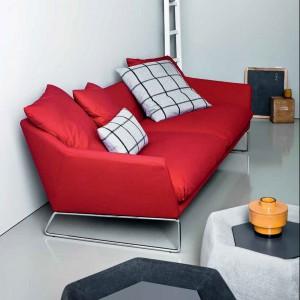 Czerwona sofa znakomicie pasuje do szarego salonu. Fot. Saba.