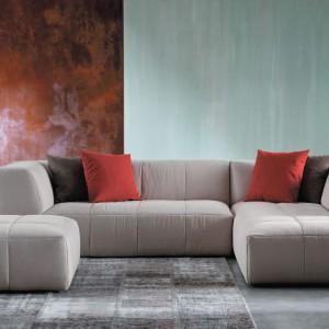 Miedziany fragment ściany oraz poduszki o tym samym odcieniu ocieplają jasną szarość. Fot. Divanidea.