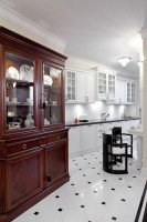 Kuchnię od połączonego z jadalnią salonu oddziela ścina  z wysoką zabudową kuchenną. W ścianę wbudowano lodówkę side by side i piekarniki. Meble w kuchni zostały zaprojektowane tak, aby komponowały się z meblami w salonie i jadalni.