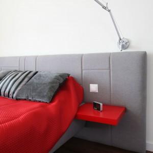 Szare łóżko z tapicerowanym zagłówkiem oraz lekkie, czerwone półki stanowią funkcjonalne rozwiązanie. Proj.Iza Szewc. Fot.Bartosz Jarosz.