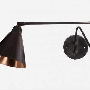 Kinkiet Game wykonany ze stali w kolorze białym lub czarnym, wnętrze lampy w kolorze miedzianym. Fot.House doctor.