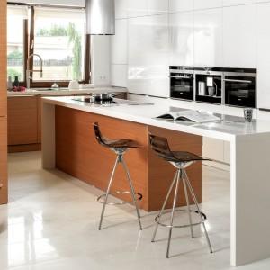 Kuchnia – model 006 wykończona jest naturalnym fornirem w odcieniu różanym oraz białym błyszczącym lakierem o ciepłym odcieniu. Całość dopełnia blat z konglomeratu kwarcowego. Zabudowa kuchenna przechodzi płynnie w zabudowę korytarzową, którą wykończono tym samym fornirem. Wycena indywidualna, Zajc Kuchnie.