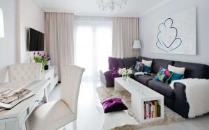 Salon w jasnej kolorystyce, z akcentami w kolorze niebieskim i fioletowym. Biel jest tutaj głównym kolorem i nadaje wnętrzu szyk i elegancję. Dodatki w wyrazistej i intrygującej kolorystyce współgrają dobrze z bielą, sprawiając, że wnętrze nie traci przytulności. Całości dopełniają grafiki na ścianie - przykuwające uwagę swoją prostotą i pomysłem.