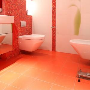 Łazienka w bieli i czerwieni jest elegancka, a przy tym pełna życia. Fot. Bartosz Jarosz.