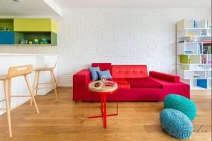 To mieszkanie czaruje różnorodnością swoich kolorów. Utrzymane w oszczędnej stylistyce, gdzie główną rolę gra biel i brąz, zyskuje swój pełen kształt poprzez dobór elementów wystroju w żywych i wyrazistych barwach oraz niejednorodnej stylistyce. Architekt brawurowo łączy ze sobą barwy i style, tworząc ciekawą i intrygującą mieszankę, wzbogaconą delikatnymi akcentami (ściana z odkrytą i pobieloną cegłą).