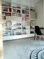Biblioteka - gabinet w domu jednorodzinnym. Mebel zaprojektowany dla książek, zyskuje dynamiczny podział dzięki różnym wysokością wnęk oraz kubikom wpasowanym pomiędzy półki. Biblioteka jest miejscem do pracy i relaksu.
